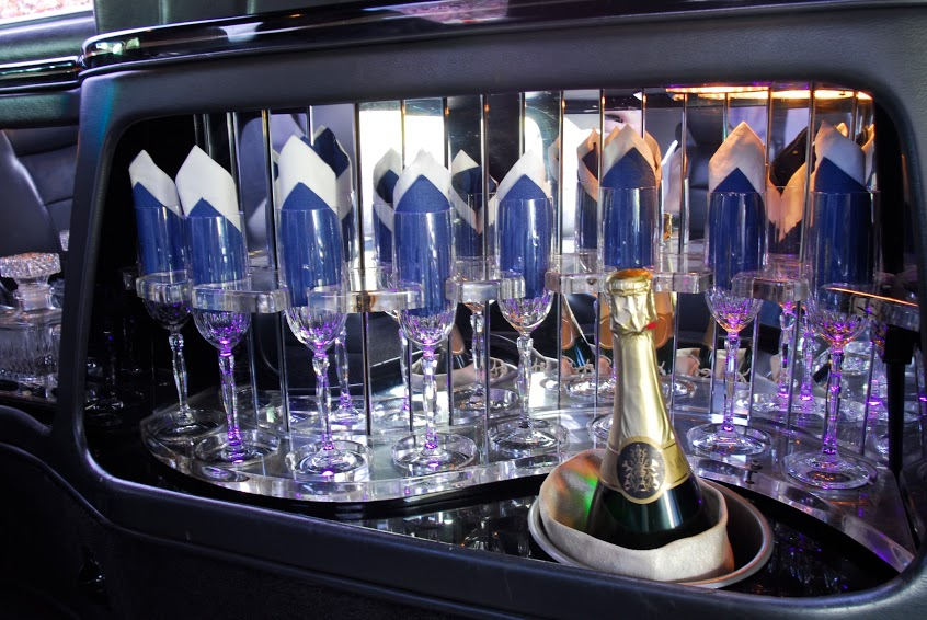 Champagne and glasses in luxury limo hire setting from Manchester Wedding Cars.